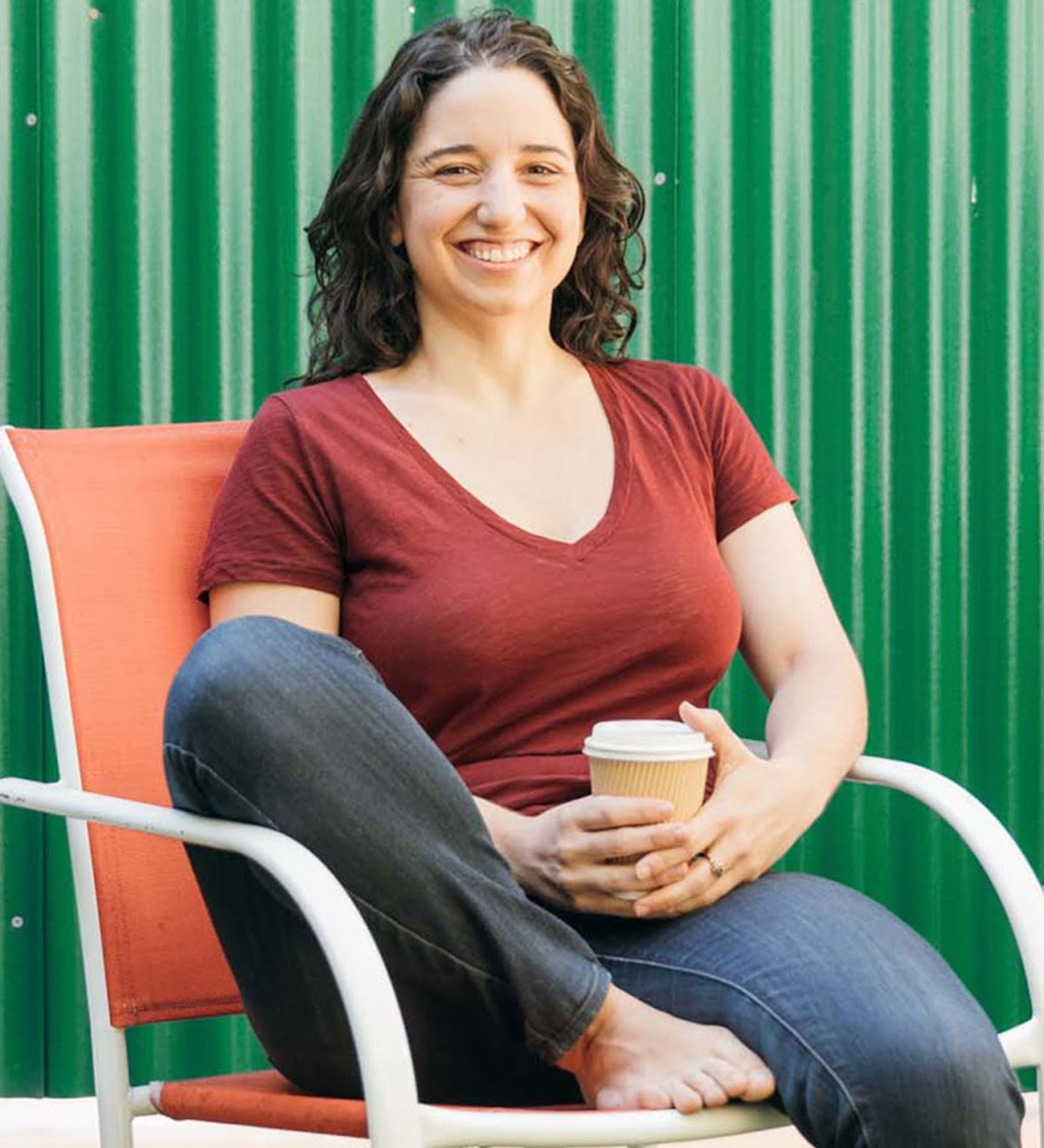 Noga Leviner, Co-Founder and CEO of PicnicHealth, smiles while sitting in a chair outdoors.