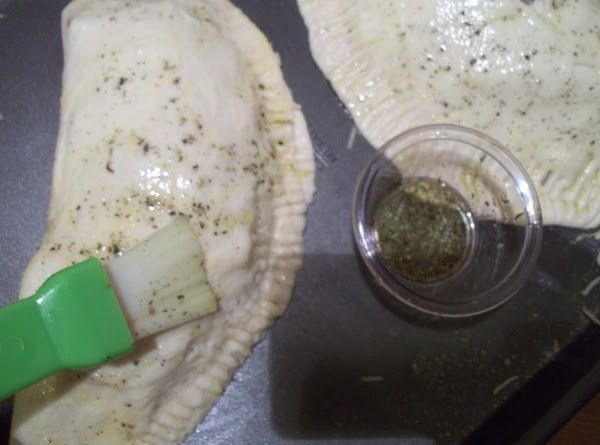Using a pastry brush, brush the dough with the olive oil/ seasoning.