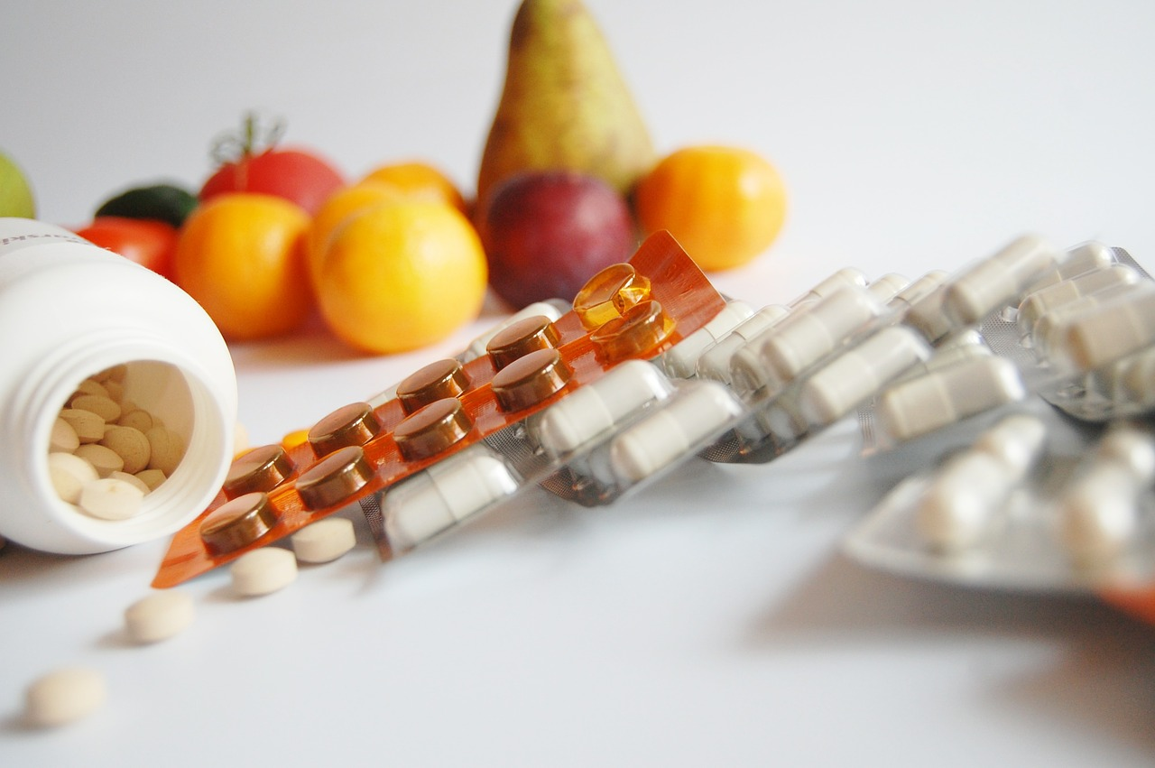 vitamin, supplements, and fruits in the background