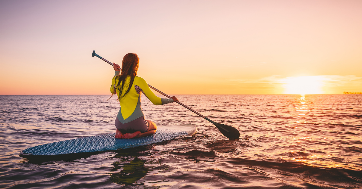 A woman trying paddleboarding while watching the sunsate
