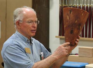 """Photo: Phil explained that it was turned endgrain so that you can see the """"Rings of Time"""" as you look in it.  Here he points to the pith strategically placed off to the side to avoid a crack in the bottom."""