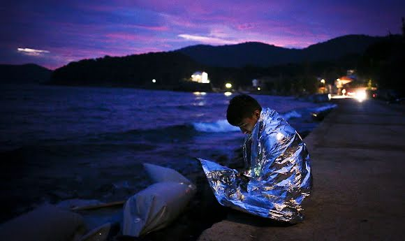 Un réfugié syrien est assis en bord de mer à la nuit tombante enveloppé dans une couverture.