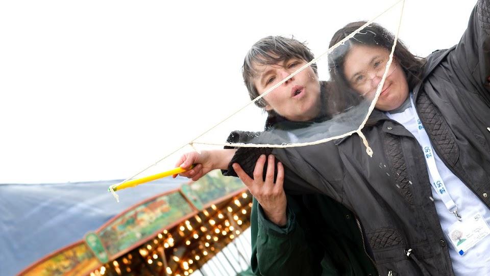 personne handicapée et accompagnant faisant des bulles dans une fête foraine