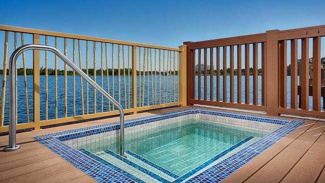 An outdoor deck featuring a hot tub that overlooks Disney's Contemporary Resort and Seven Seas Lagoon
