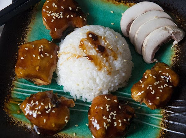 Place the chicken on a bed of white rice, and sprinkle with the sesame...