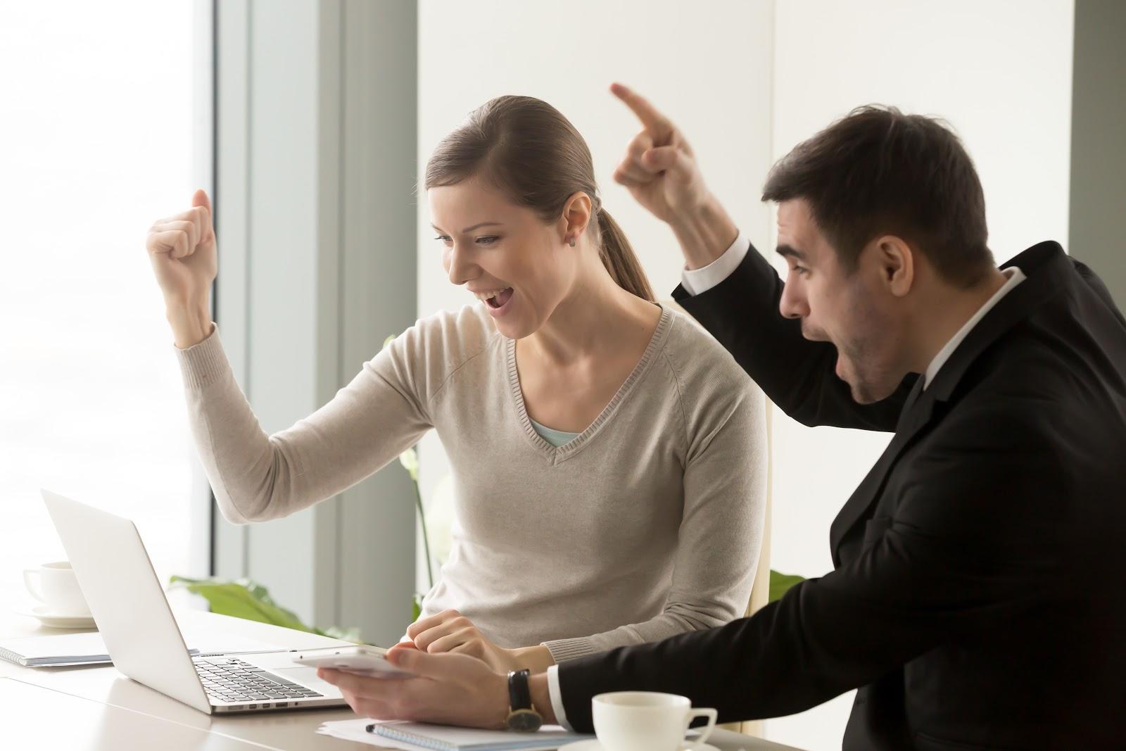 Dois jovens colegas de trabalho comemoram resultados na frente de um notebook