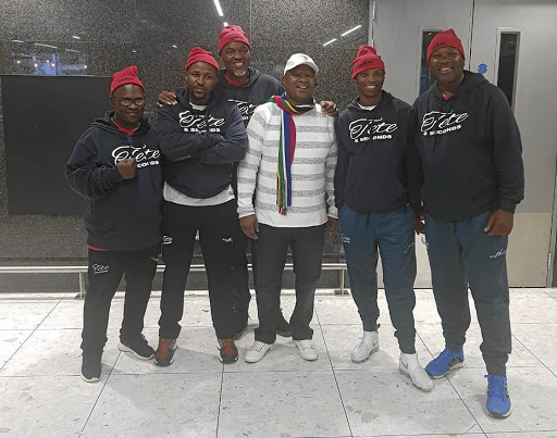Champion Zolani Tete, second from right, and his team were met at their hotel by SA ambassador Ahlangene Sigcawu (white top).