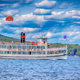 The Mohican on Lake George by Debbie Quick - Transportation Boats ( blue sky, debbie quick, natural, nature, adirondacks, nature lovers, clouds, lake george village, water, trees, debs creative images, new york, boat, national geographic, american flag, transportation, blue, mohican, boating, sailing, lake, lake george, landscape,  )