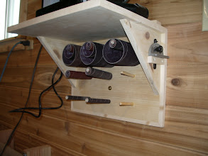 Photo: It's mounted just above and behind my oscillating spindle sander. The dowels hold the spare sanding sleeves.