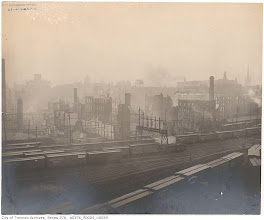 """Photo: Railway lines at the south end of the Toronto fire of 1904. Looking N, west of Bay. Taken April 22, 1904. """"The tall smokestack of the Eckardt company (see previous photograph) can be seen at the extreme left. The tall smokestack at the right of the picture belongs to the M. McLaughlin & Co. mill, as does the stone building just in front of it. The two water tanks on the skyline at the centre of the picture mark the Kilgour Brothers factory."""" - City of Toronto Archives"""