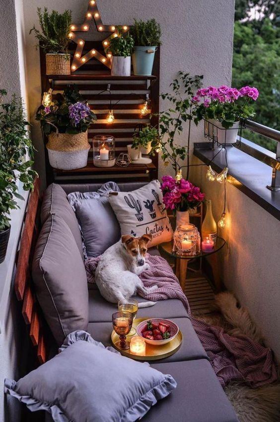 Varanda com sofá de pallet com estofado cinza, mesinha de canto com velas, armário de madeira com vasos de plantas, objetos iluminados e varal de lâmpadas compondo a decoração.