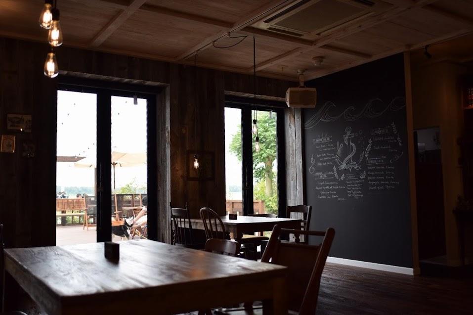 新舞子のカフェ「ネストバイザシー」店内からテラスを眺める