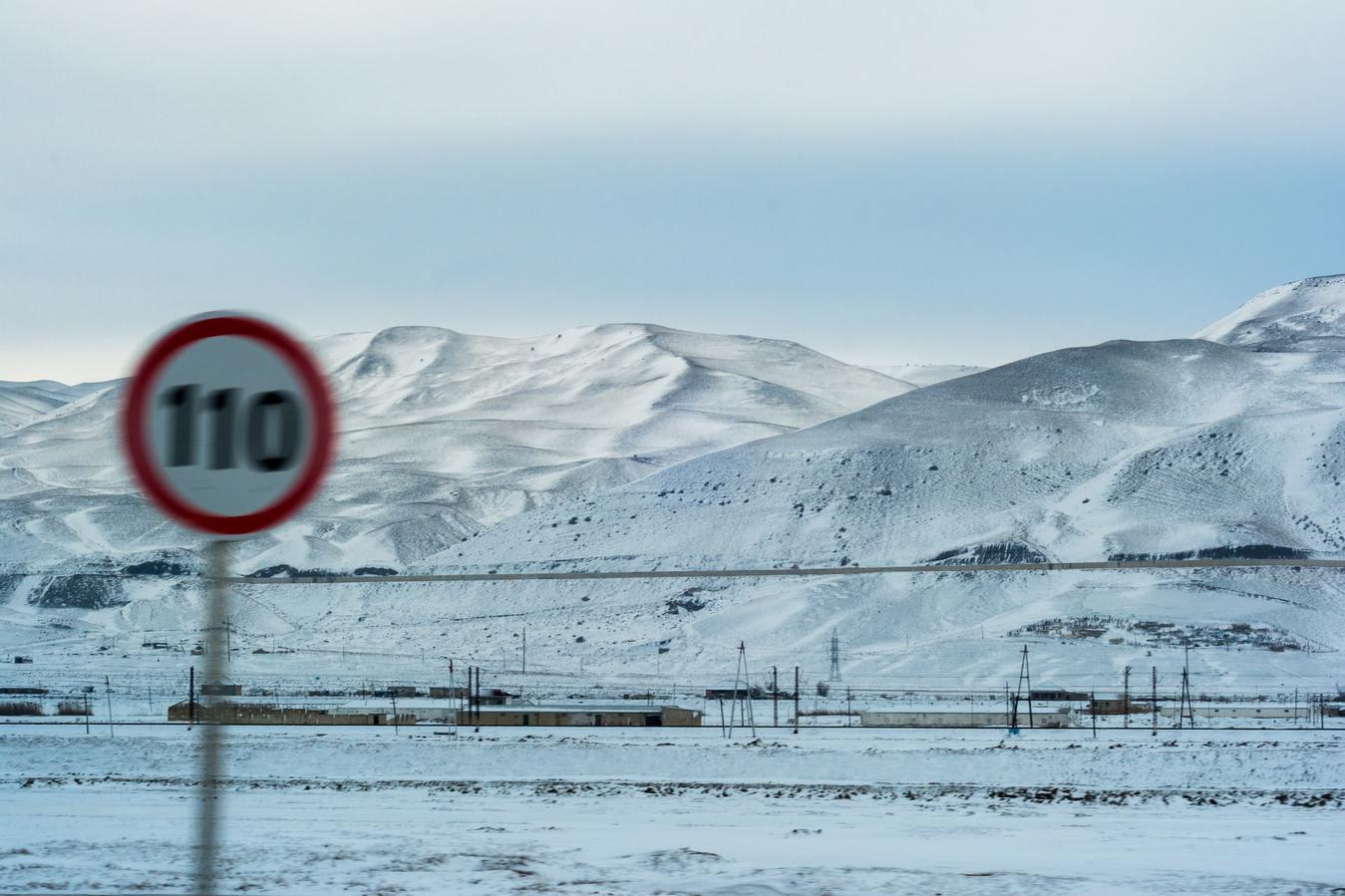 Śnieżny krajobraz ze znakiem ograniczenia prędkości, który jest zamazany