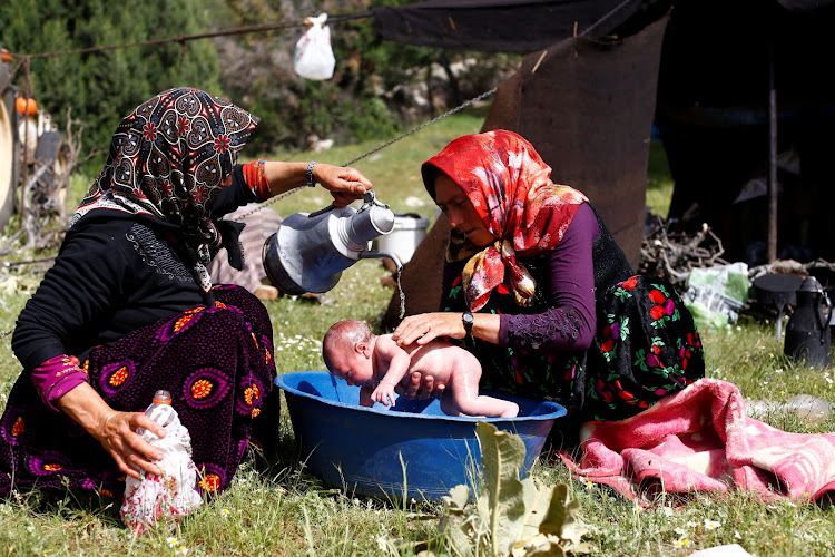Rukiye Gobut washes her 20-day-old baby Efe Gobut near Konya, Turkey. Every year, nomads start walking from Mersin on the Mediterranean coast with more than a thousand goats, travelling to the central Anatolian province of Konya.