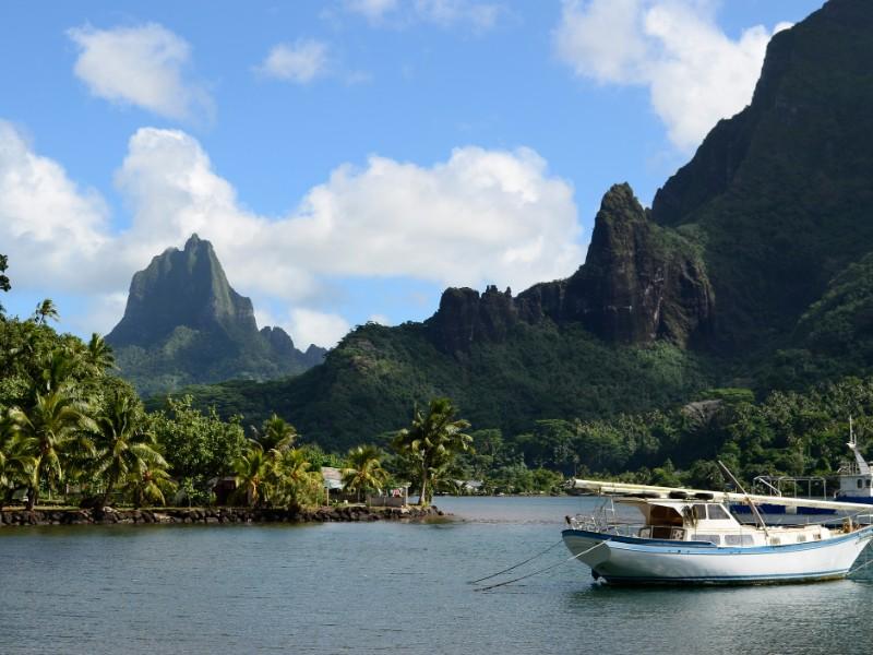 Barco em Cooks Bay, com a montanha Moua Puta em segundo plano na ilha pacífica tropical de Moorea, perto do Tahiti