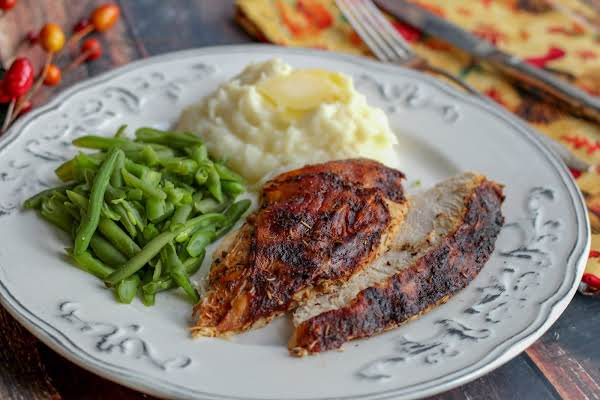Slices Of Herb Rotisserie Turkey Breast On A Plate With Green Beans And Mashed Potatoes.