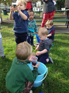 Children doing a scooping activity in a park