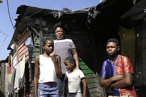 From left, Khanyisa, Solani, Victoria and Songayi Dave Rivele outside their small shack in Alex, Johannesburg. Solani has her sights set on a plot in Waterfall.