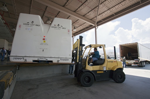 A forklift moves shipping containers packed with tools and flight support equipment for their trip to the Japanese Aerospace Exploration Agency's Tanegashima Space Center.
