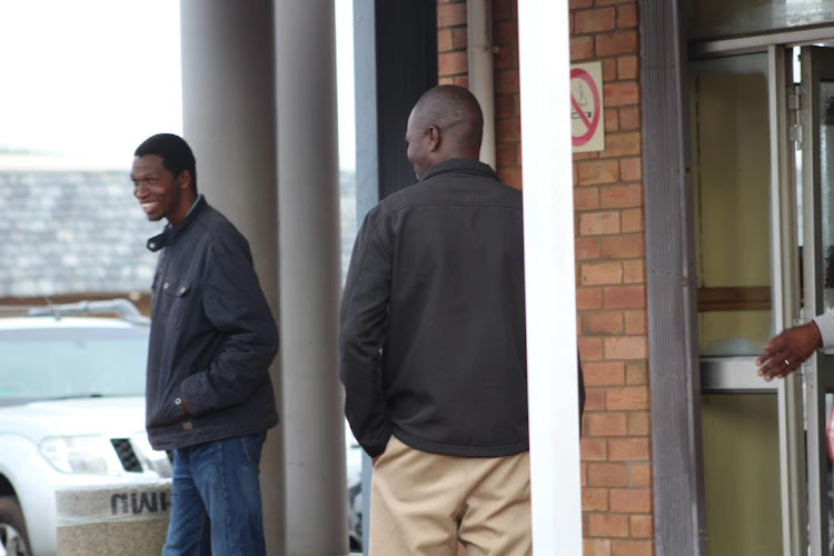 Alleged rhino poacher Muntogokwakhe Khoza turns his back to avoid being photographed while leaving the Richards Bay Magistrates Court earlier this month. Pictured with him is co-accused Ayanda Buthelezi.
