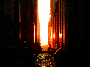 """Photo: """"Supernova...""""  There is nothing quite like the intensity of seeing the sun spread it's light like wildfire through the streets of midtown Manhattan. The red light glows with the ferocity of a supernova showering its splendor onto the urban landscape.  In honor of tonight's Manhattanhenge sunset which may or may not be hidden by storm clouds since New York City's weather has been highly unpredictable and stormy as of late, this is a photo I took exactly a year ago during last year's Manhattanhenge. The buildings in this photo are the buildings in Times Square (you can make out the Madame Tussauds sign).  Manhattanhenge is a semiannual occurrence in which the setting sun aligns with the east–west streets of the main street grid in the borough of Manhattan in New York City. The term is derived from Stonehenge, at which the sun aligns with the stones on the solstices. It was coined in 2002 by Neil deGrasse Tyson, an astrophysicist who is the director of the Hayden Planetarium at the American Museum of Natural History.  —-  I was really overwhelmed by the response to my post yesterday about the difficulties of monetizing photography (or anything) online: http://goo.gl/n9e9c . I posted it, thought about deleting it more than a dozen times, walked away for a few hours last night to get some things done and came back to a flood of responses. I am mostly floored by the experiences shared with me that are so similar in scope to what I have been through.  I will reply to all the comments and emails today and tomorrow when I have the time. I wrote the post because I saw a lack of discourse on the painful realities of social media and online marketing. I didn't realize how much it would resonate with people. Thank you so much to all who weighed in on the discussion.    New York Photography: Manhattanhenge sunset overlooking Times Square.    You can view this post along with information on purchasing prints of this image if you wish at my site here:  http://nythroughthele"""