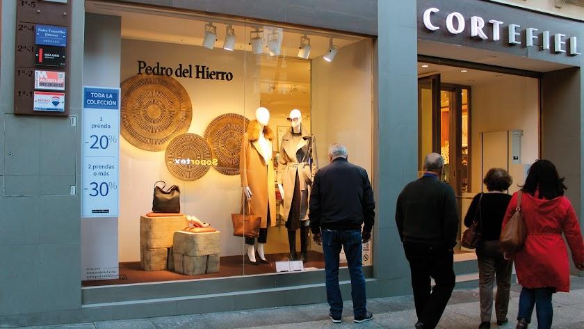 La ropa de abrigo aguarda a los clientes en los escaparates del Paseo, esperando las primeras noticias del invierno.