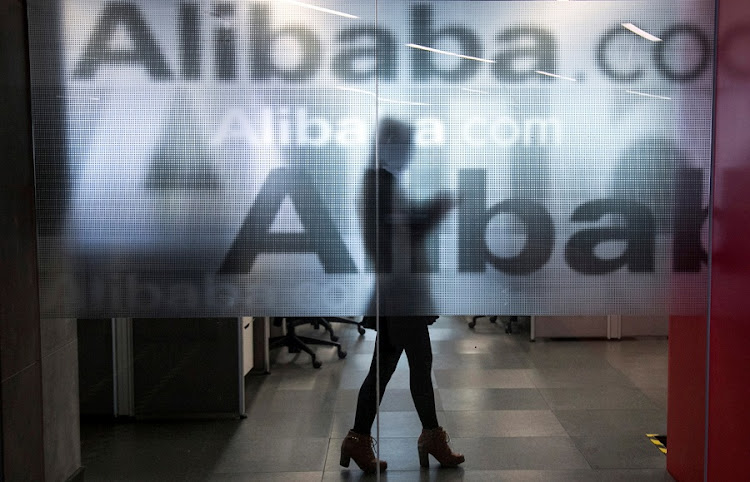 An employee walks behind a glass wall with the logo of Alibaba at the company's headquarters on the outskirts of Hangzhou, Zhejiang province, China. Picture: REUTERS/CHANCE CHAN