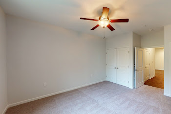 Bedroom with plush carpet, closet, ceiling fan, and neutral colored walls
