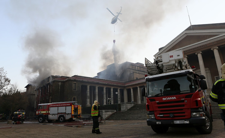 A helicopter water-bombs the fire near the Jagger Reading Room at the University of Cape Town.