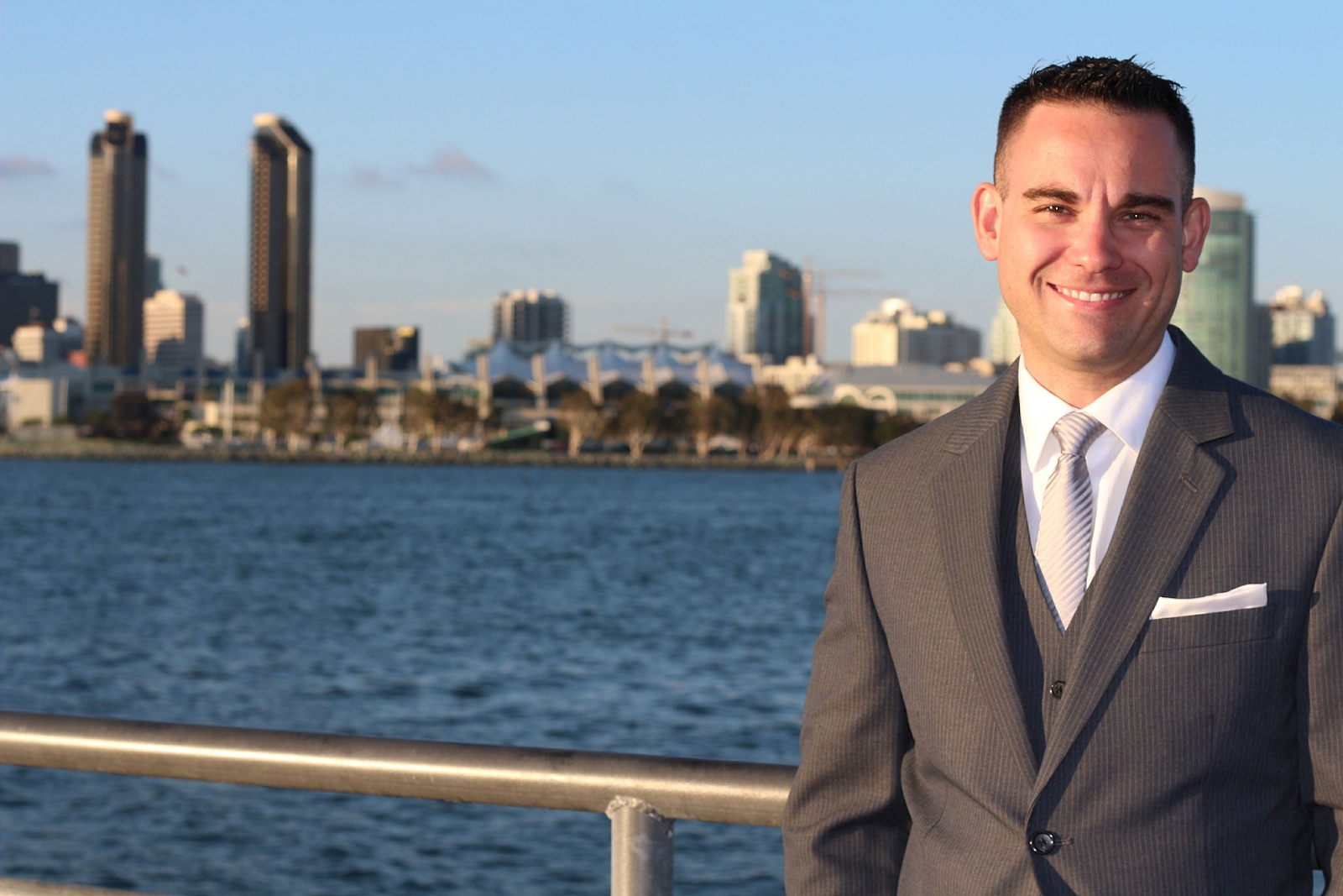 smiling man in suit with river behind him