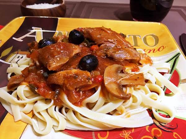 A Chicken Mixture Served Over Cooked Linguine.