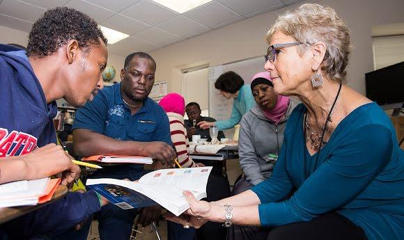 Un trabajador de campo de Social Finance muestra un libro abierto a dos estudiantes de una minoría