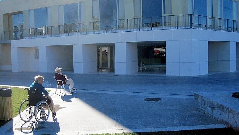 Una mujer en silla de ruedas toma el sol junto a un hombre a las puertas de una residencia de mayores.