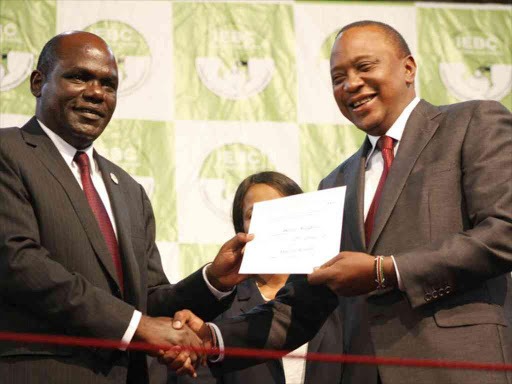 IEBC chairman Wafula Chebukati hands President Uhuru Kenyatta his certificate following the announcement of the winner of the repeat election, October 30, 2017. /MONICAH MWANGI