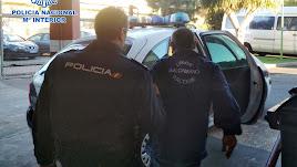 Un agente, conduce al detenido hasta un vehículo de la Policía Nacional.
