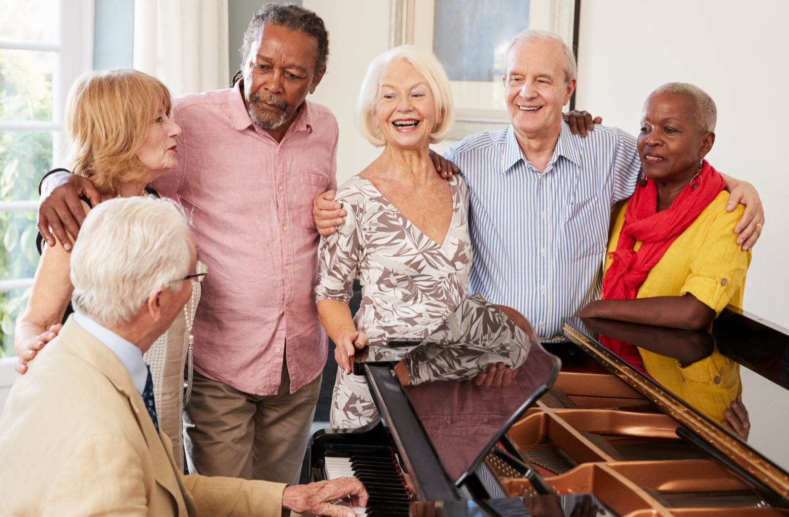 A group of fully vaccinated people gathering around the piano in their Kaplan senior living community