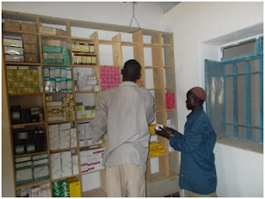 Photo: Workers at the Wunlang Clinic stock shelves with medical supplies. Our grant pays for temporary nursing and support staff for the clinic until it can sustain itself from government support and modest patient fees for treatment at the clinic.