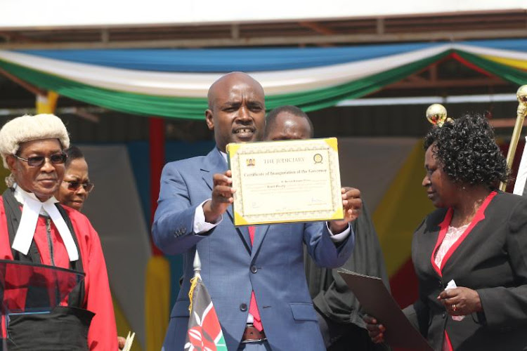Bomet Governor Hilary Barchok shows to the crowd the certificate of office during the swearing ceremony at Bomet Green stadium on Thursday, August 8, 2019.
