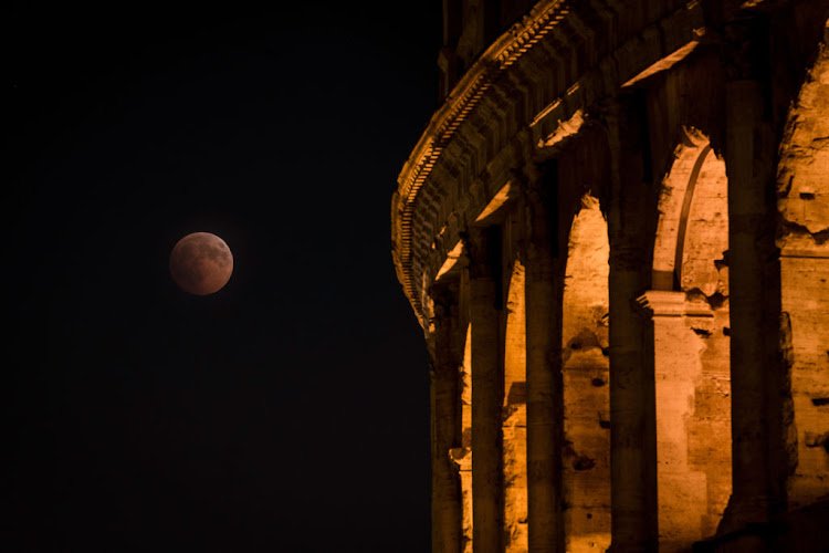 A total lunar eclipse is seen up the sky near the Colosseum on July 27 2018 in Rome, Italy. T (Photo by Awakening/Getty Images)