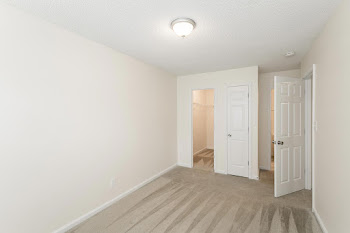 Bedroom with light carpet and large closet