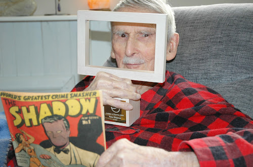 Peter Chapman with his Ledger of Honour and the first edition of his famous comic The Shadow.