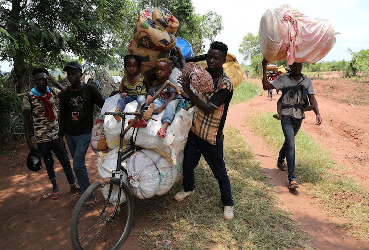 Congolese migrants expelled from Angola push a rented bicycle to transport their children and belongings along the road to Tshikapa, Kasai province near the border with Angola, in the DRC, October 12 2018. Picture: REUTERS/GIULIA PARAVICINI