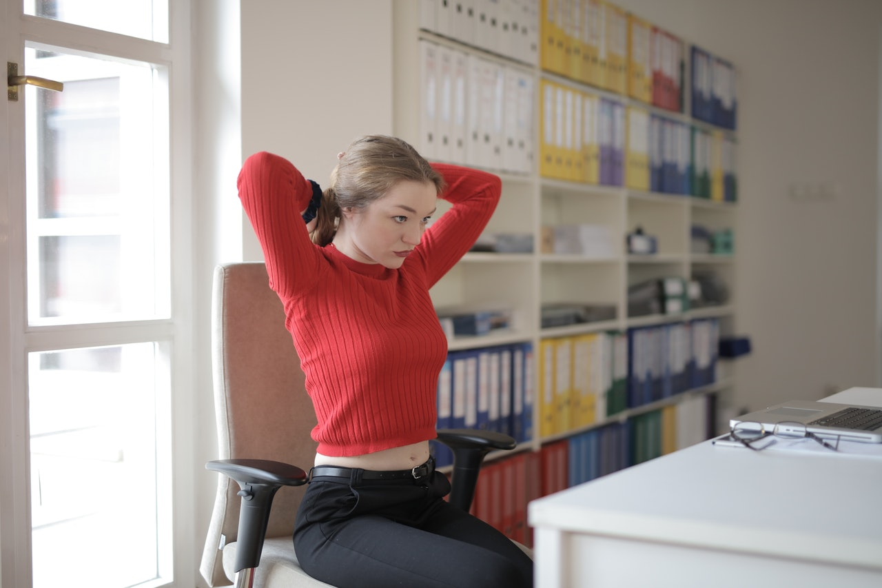 Woman lifting arms up at the desk to start a desk exercise