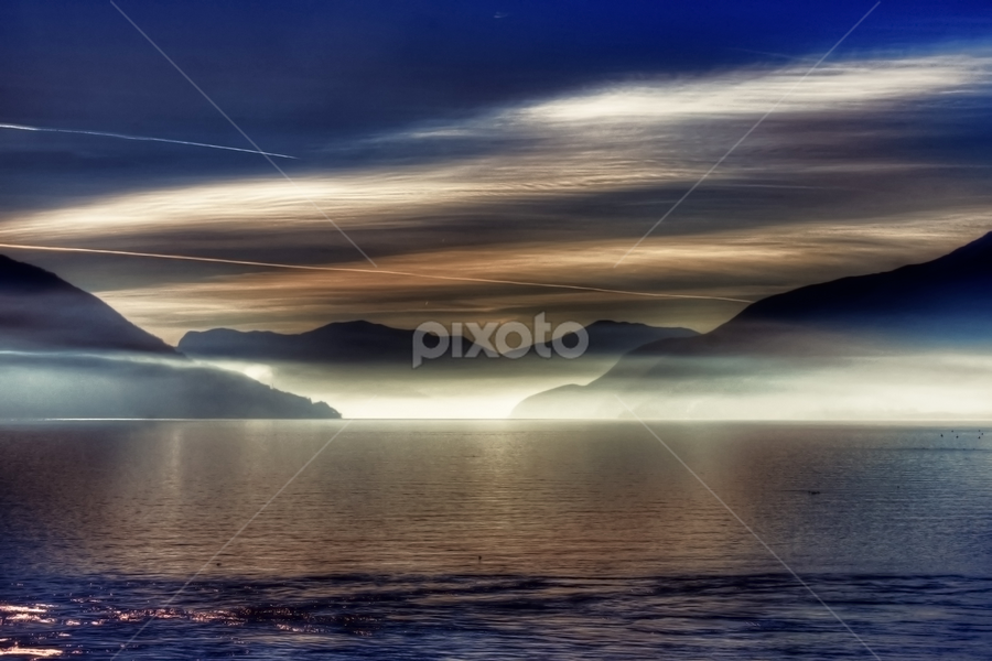 Lake Maggiore by Joana Kruse - Landscapes Sunsets & Sunrises ( travel; travelling; europe; tourism; vacation; holiday; lago maggiore; lake maggiore; mountain; mountains; alps; panorama; in the morning; morning; mist; misty; morning mist; mysterious; mood lighting; sunlight; clouds; sky; isole di brissago; brissago islands )