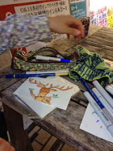 Photo: テーブルでハガキサイズの絵を描く中村俺様さん