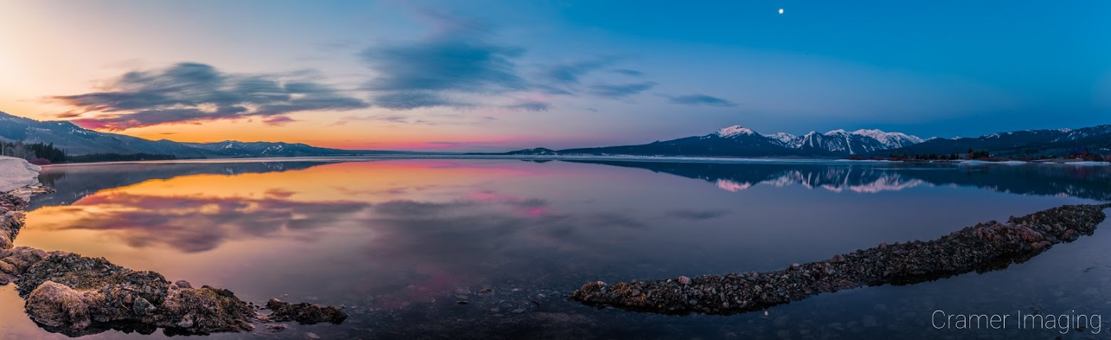 Cramer Imaging's professional quality landscape panorama photograph of the sky and moon reflecting in Henry's Lake at dawn with blue and golden hours