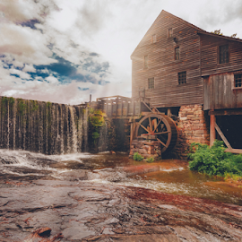 Yates Grist Mill by Steve Friedman - Buildings & Architecture Public & Historical ( north carolina, waterfall, historical, grist mill, clouds, sun streaks )