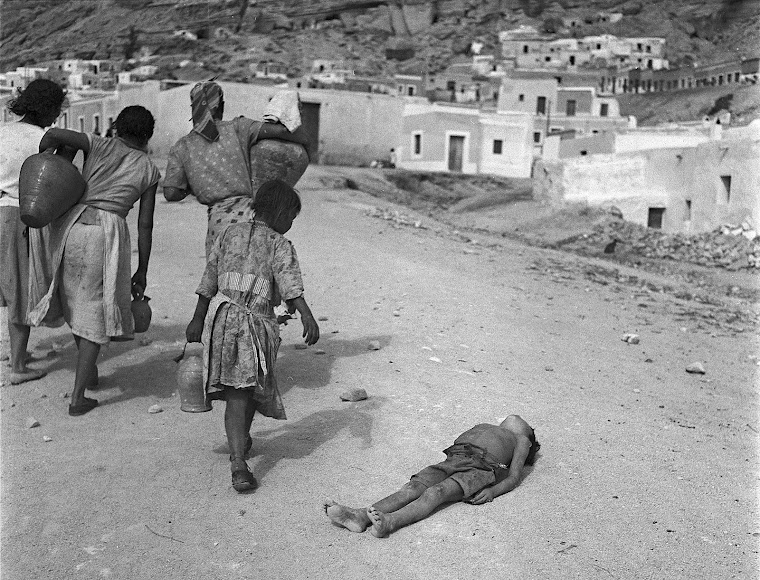 En 1962, mujeres y una niña transportan agua en vasijas mientras un niño yace tumbado en el suelo.