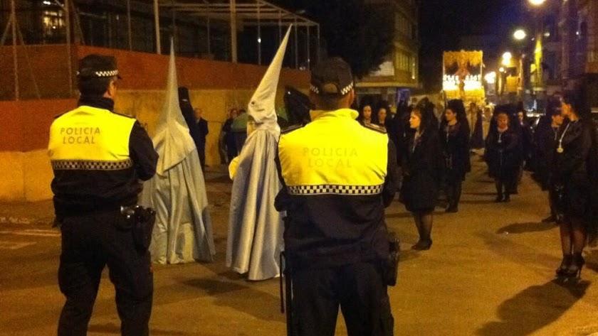 Dos policías locales, al paso de una procesión en Almería.