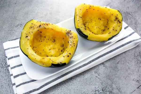 Two Halves Of Acorn Squash On A Plate.